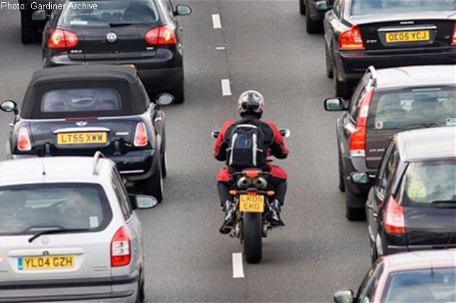 A motorcyclist filters through heavy traffic on the UK's M25 motorway